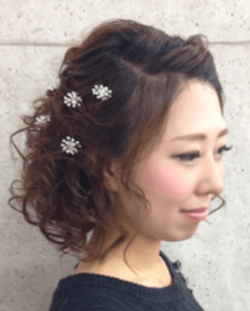 入学式でスーツに合うレディースの花飾り揺る巻きカールの髪型