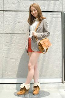 7グレーのテーラードジャケット×オレンジショートパンツ×白ブラウスのコーデ