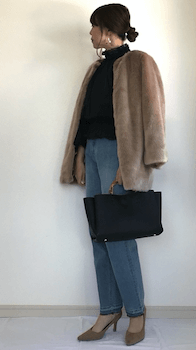 ベージュのファーコート×黒のタートルネック×デニムパンツ×ベージュのパンプス×バンブーバッグの秋冬のコーデ