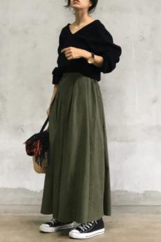 緑のフレアスカート×黒のVネックニット×黒のスニーカー