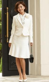 白のジャケット×フリルブラウス×白パンプス×黒のバッグ×ベージュのコサージュ