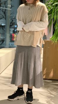 ベージュのケーブル編みのニットベスト×シャツ×プリーツスカート×スニーカー