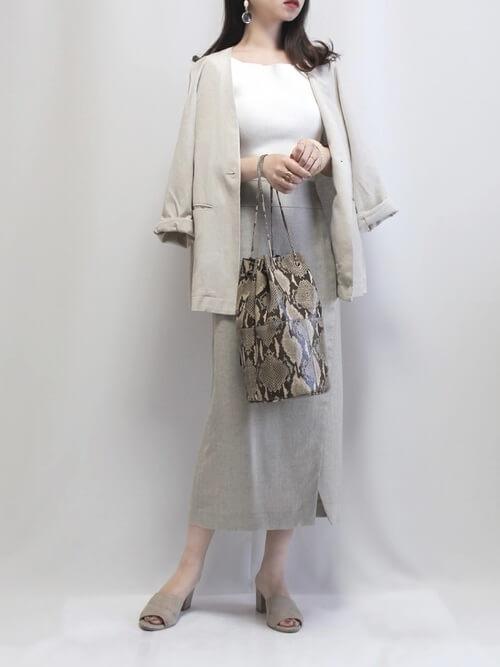 白のジャケット×白のカットソー×ベージュのタイトスカート×バイソン柄のバッグ