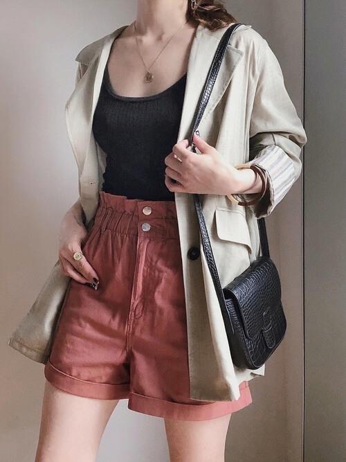 ベージュのジャケット×黒のタンクトップ×オレンジのショートパンツ×黒のバッグ