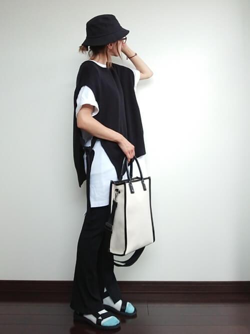 バイカラーの靴下×スポーツサンダル×黒のフレアパンツ×黒のニットベスト×白のカットソー
