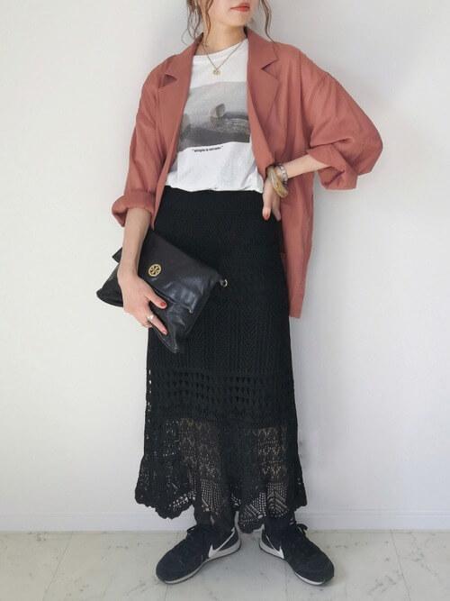 ブラウンジャケット×白のグラフィックTシャツ×黒のニットスカート×黒のスニーカー×黒のクラッチバッグ