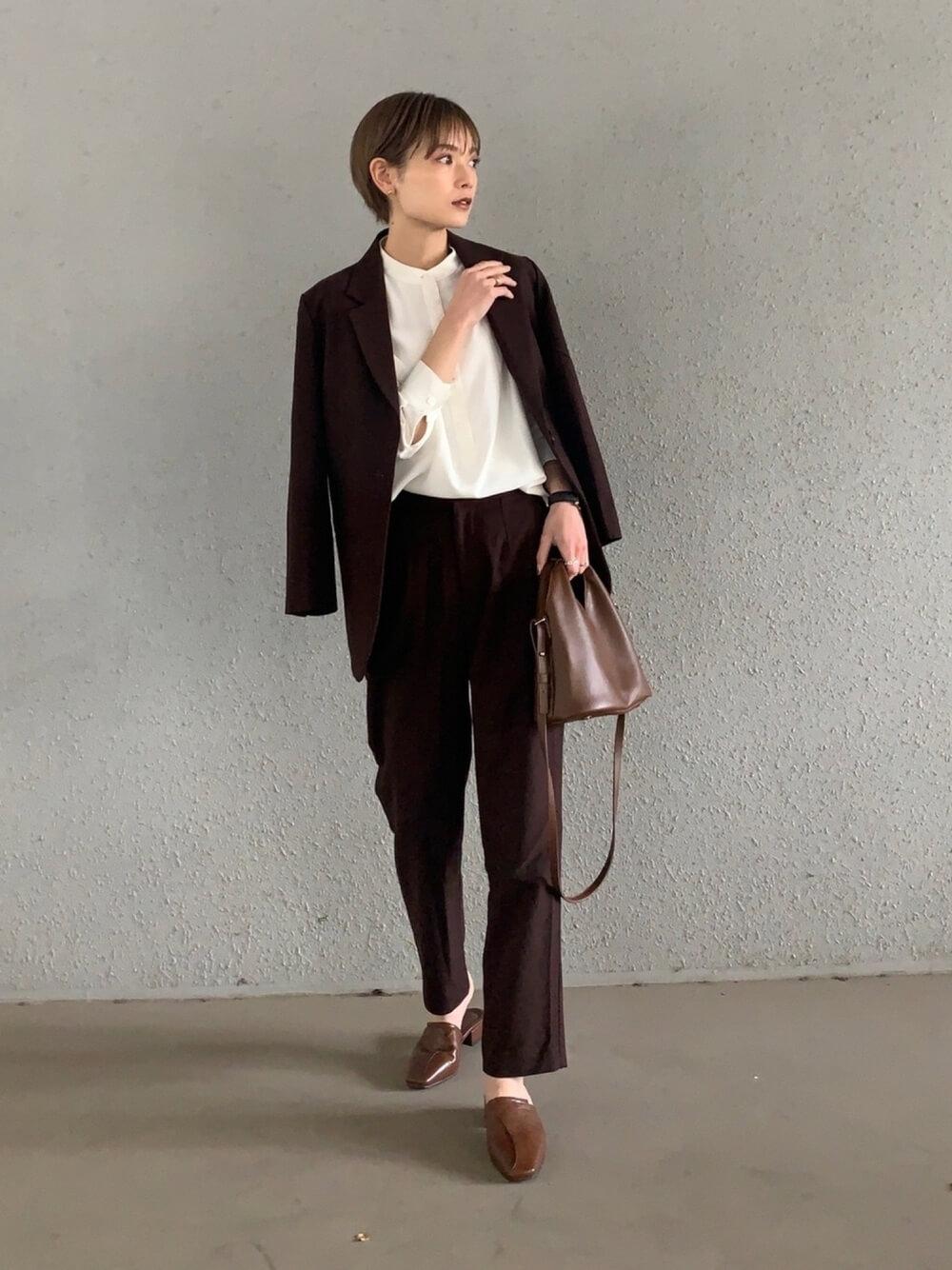 ダークブラウンのテーラードジャケットのセットアップ×白のバンドカラーシャツ×レザーのサボサンダル