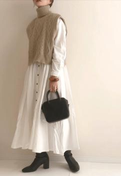 白のロングワンピース×ベージュのタートルニットベスト×黒のブーツ×黒のバッグ