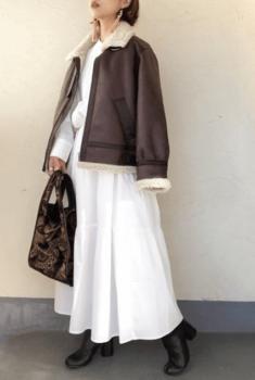 白のロングワンピース×ムートンジャケット×黒のブーツ×ジャガード織りバッグ
