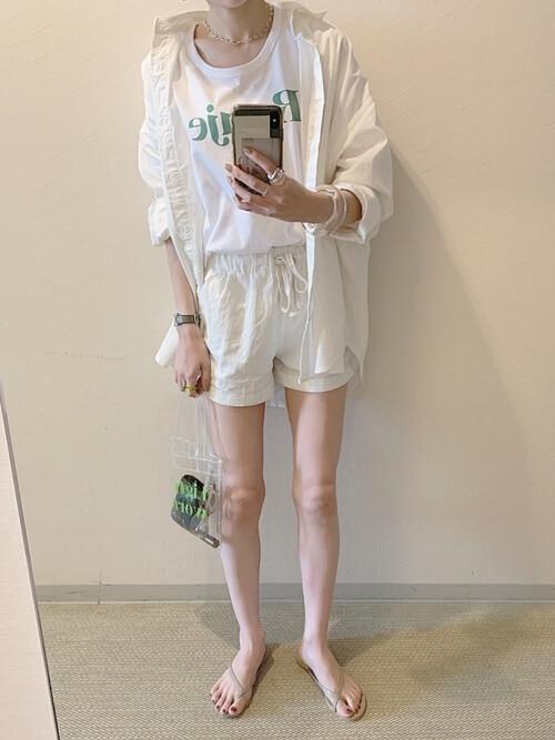 白のショートパンツ×白のシャツ×白のロゴTシャツ×ベージュのサンダル×クリアバッグ