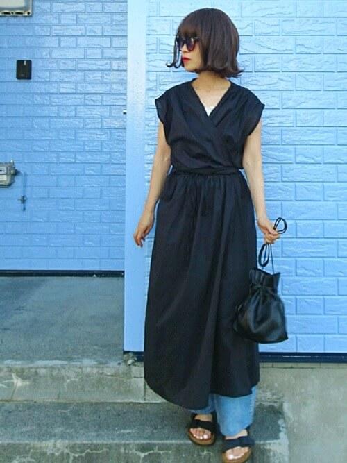 カシュクールワンピース×デニムパンツ×黒のサンダル×黒の巾着バッグ
