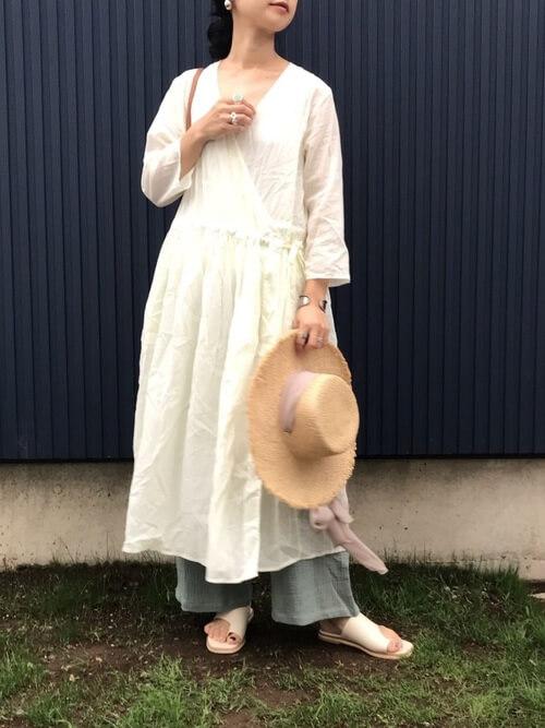 カシュクールワンピース×グレーのリラックスパンツ×白のサンダル×麦わら帽子