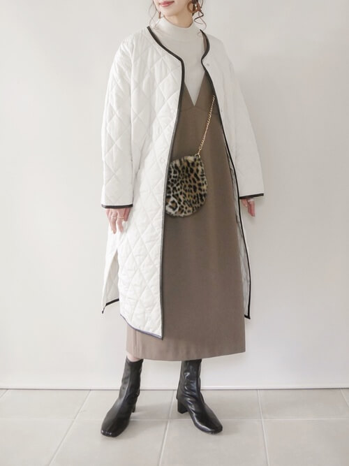 ジャンパースカート×白のキルティングコート×白のハイネックニット×黒のブーツ