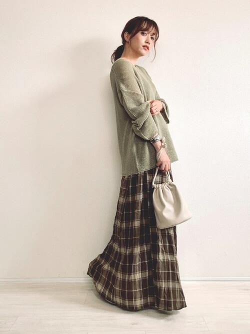 グリーンのニット×チェックのロングスカート×白の巾着バッグ