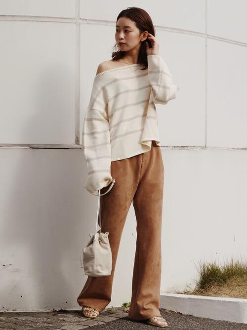 白のサマーニット×ブラウンのフレアパンツ×ベージュのサンダル×ベージュの巾着バッグ