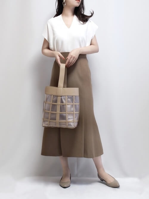 白のサマーニット×ベージュのスカート×ベージュのパンプス×クリアバッグ