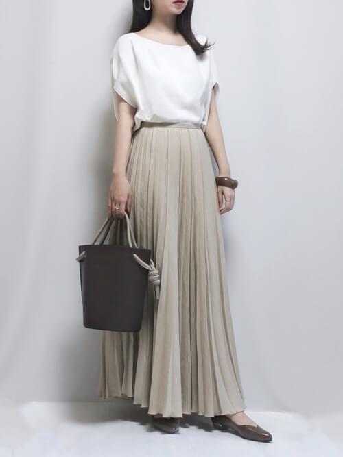 白のサマーニット×ベージュのプリーツスカート×ブラウンのパンプス×黒のバッグ