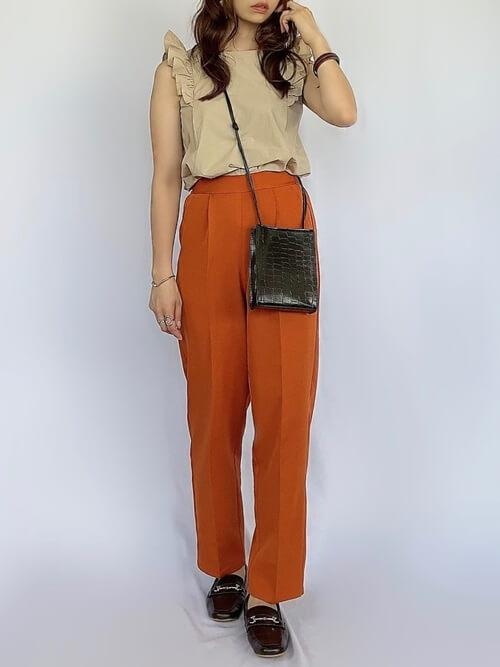 袖フリルトップス×オレンジのテーパードパンツ×黒のローファー×黒のショルダーバッグ