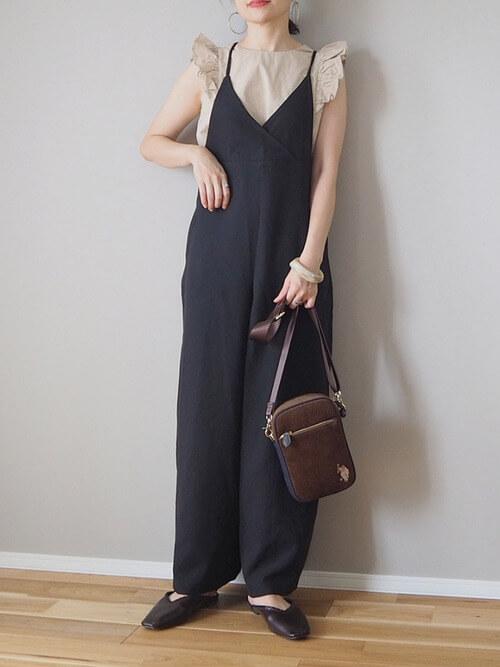 袖フリルトップス×黒のサロペットスカート×黒のパンプス×ブラウンのバッグ