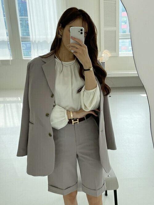 テーラードジャケット×白のブラウス×グレーのショートパンツのコーデ
