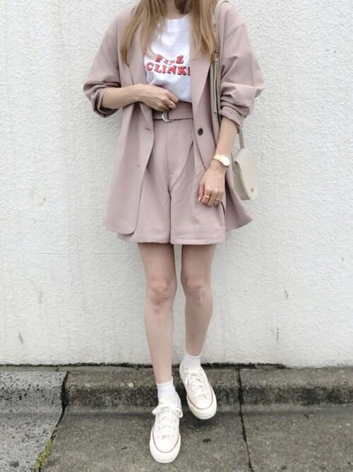 ピンクのショートパンツ×ピンクのテーラードジャケット×白のロゴTシャツ×白のスニーカー