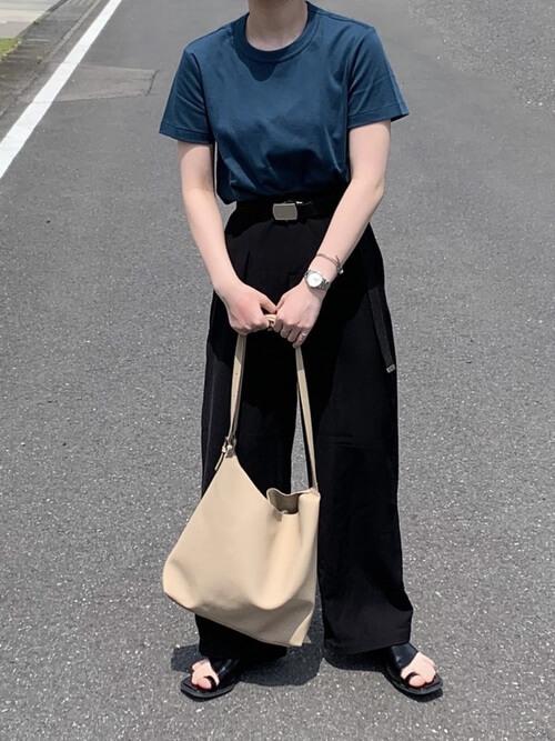 青のTシャツ×黒のスラックス×黒のサンダル×ベージュのバッグ
