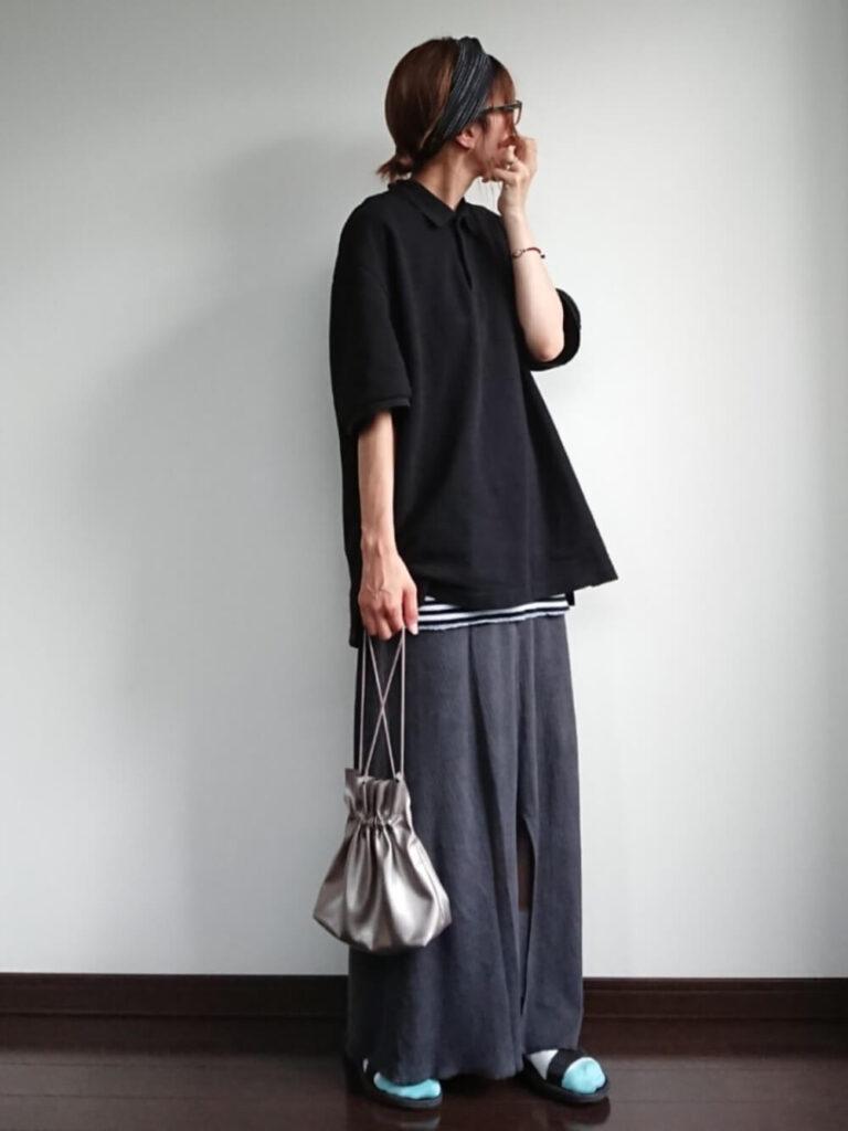 グレーのマキシスカート×サンダル×黒のポロシャツのコーデ