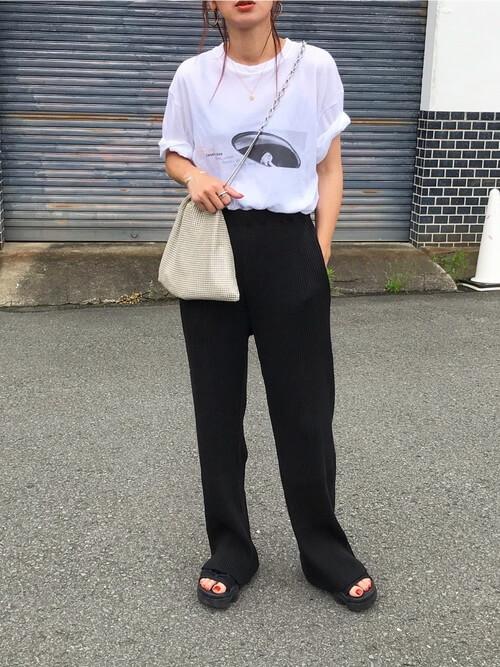 ロゴ入りの白のTシャツ×黒のリブパンツ×黒のサンダル×ベージュの巾着バッグ