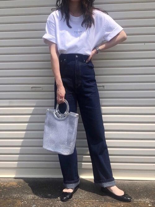 ロゴ入りの白のTシャツ×デニムパンツ×黒のパンプス×シルバーのハンドバッグ