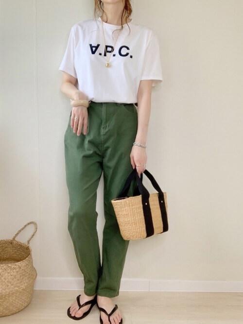 ロゴ入りの白のTシャツ×グリーンのデニムパンツ×黒のビーチサンダル×かごバッグ