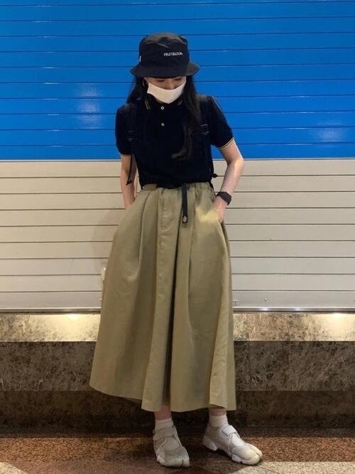 チノスカート×スニーカー×黒のポロシャツのコーデ