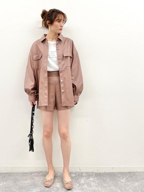 ピンクのショートパンツ×フェイクレザーのCPOジャケット×白のロゴTシャツ×ベージュのサンダル