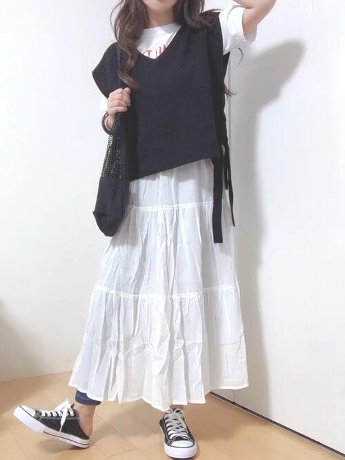 ティアードスカート×白のロゴTシャツ×黒のニットベスト×スキニーデニム×黒のスニーカー