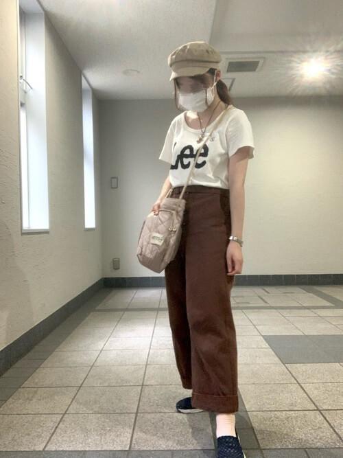白のロゴTシャツ×ブラウンのパンツ×ベージュのキャスケット×ネイビーのスリッポン