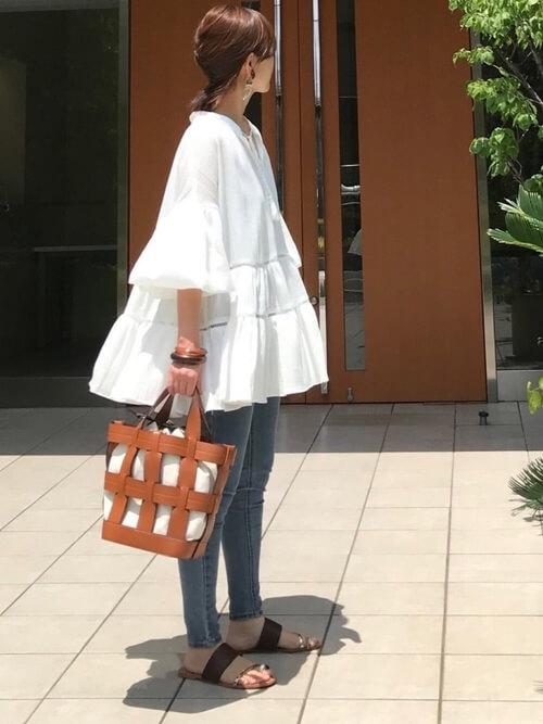 白のチュニック×スキニーデニムパンツ×ブラウンのサンダル×キャメルのネットバッグ