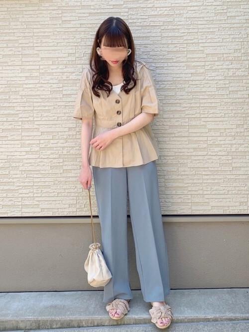 ペプラムトップス×ブルーのパンツ×ベージュのサンダル×白の巾着バッグ