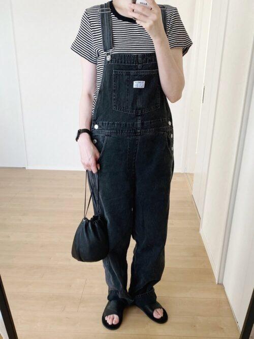 デニムのオールインワン×ボーダー×黒のサンダル×レザーの巾着バッグ