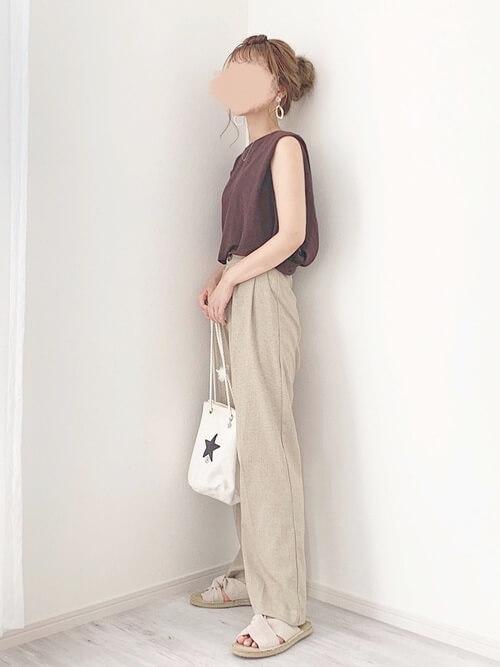 茶色のノースリーブ×ベージュのスラックスパンツ×フラットサンダルのリゾートファッションコーデ