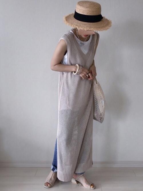 白のタンクトップ×ネットロングベスト×デニムパンツのリゾートファッションコーデ