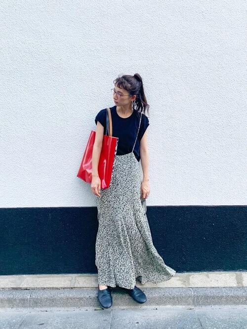 柄物のオールインワン×黒のTシャツ×黒のドレスシューズ×赤のバッグ