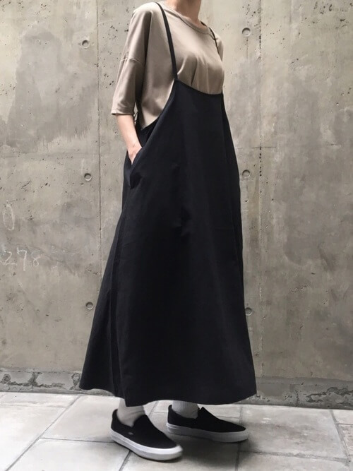 ベージュのTシャツ×黒のサロペットワンピース×黒のスリッポン