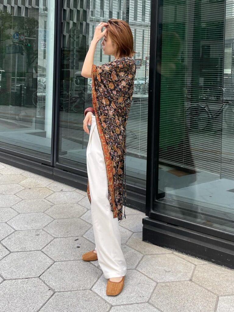 白のタックパンツ×エスニックガウン×フラットシューズのリゾートファッションコーデ