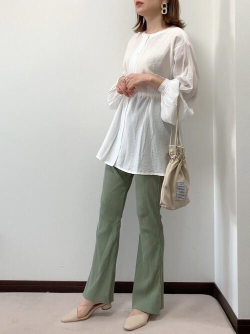 白のチュニック×グリーンのリブパンツ×ベージュのパンプス×ベージュの巾着バッグ