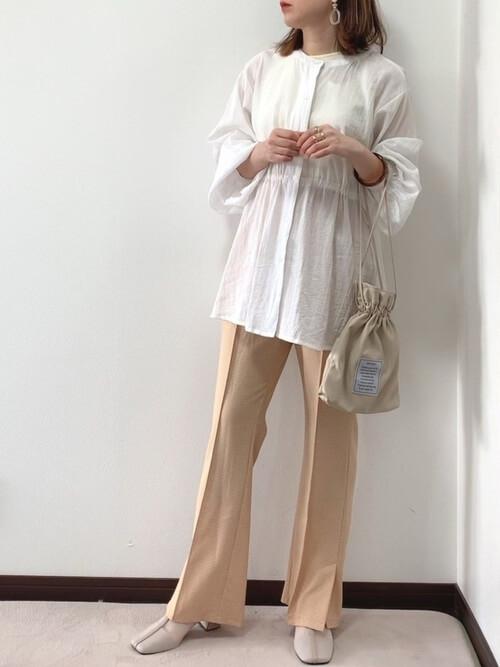 白のチュニック×ベージュのチェックフレアパンツ×ベージュのパンプス×ベージュの巾着バッグ