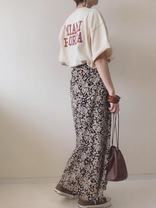 ベージュのロゴTシャツ×黒の花柄スカート×ブラウンのスニーカー