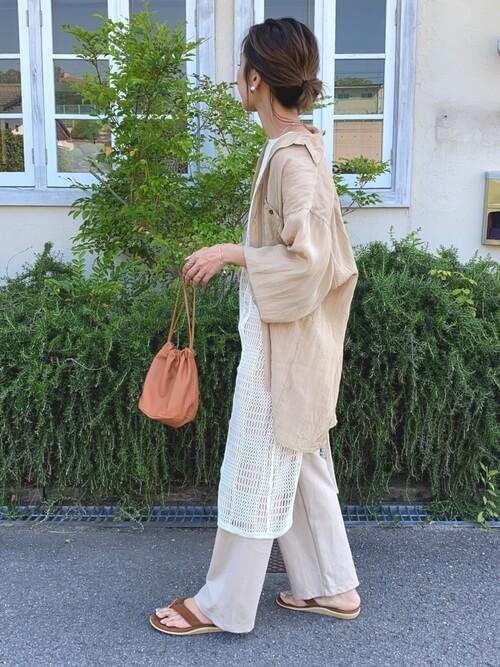 アイランドスリッパ×ベージュのシャツ×白のエプロンドレス×ベージュのパンツ