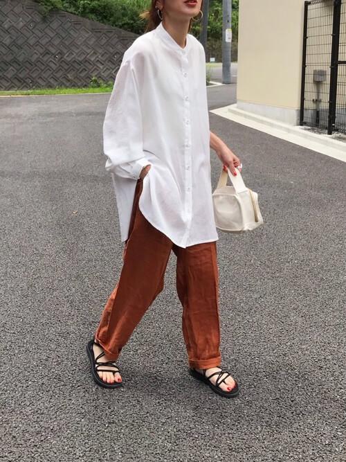白のリネンシャツ×オレンジパンツ×黒のサンダル×白のバッグ