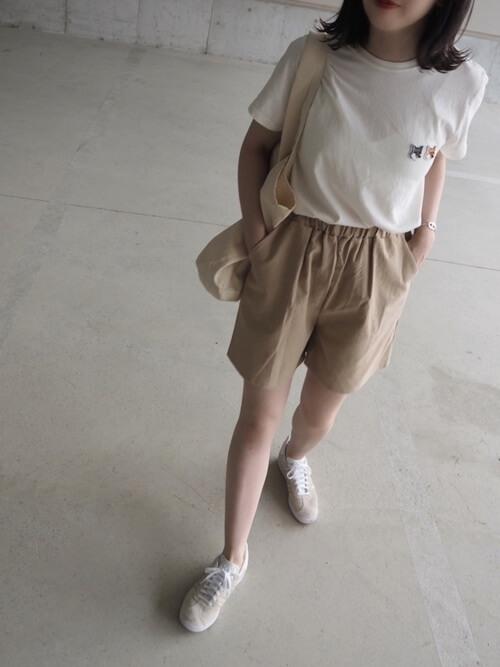 ブラウンのショートパンツ×白のTシャツ×白のスニーカー