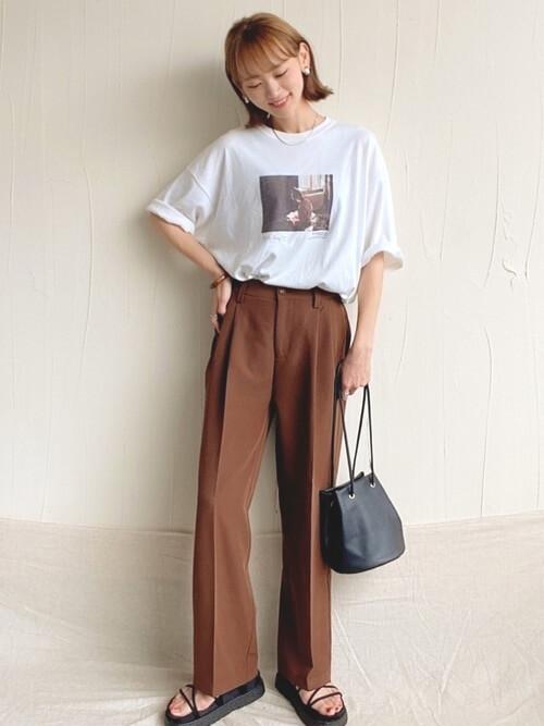 白のロゴTシャツ×ブラウンのスラックス×黒のサンダル×黒のバッグ
