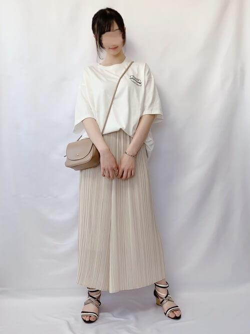 白のロゴTシャツ×ベージュのプリーツスカート×黒のサンダル×ベージュのミニショルダーバッグ